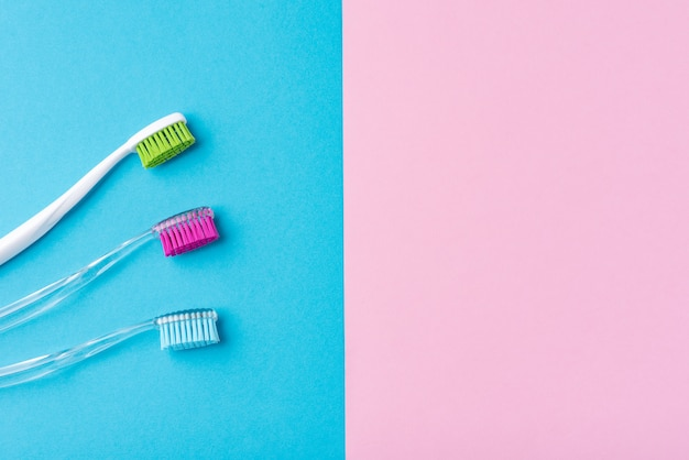 Three plastic toothbrushes on a colorful blue and pink  background, close up