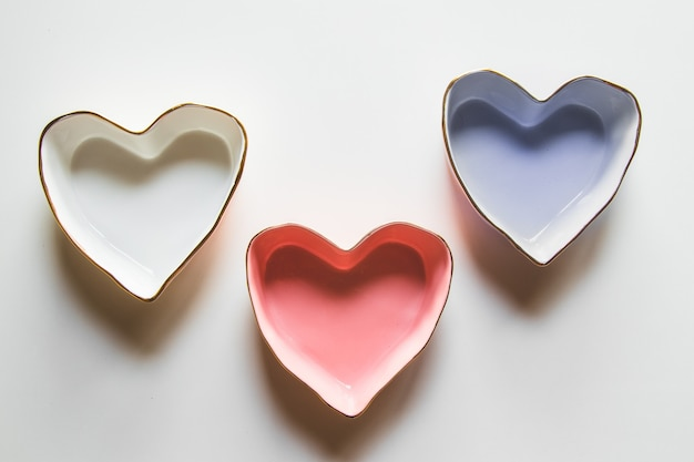 Three plates of hearts on a white background in blue, red and white.