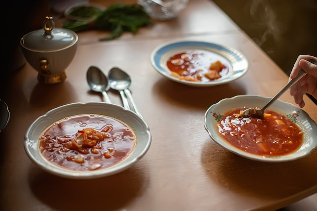 テーブルの上にボルシチが付いている3つのプレート。家族で昼食。白い皿の最初の料理。