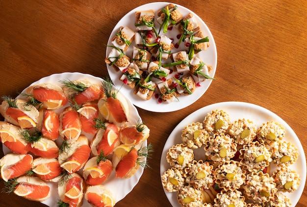 Три тарелки с вкусными закусками и закусками на деревянном столе в кафе
