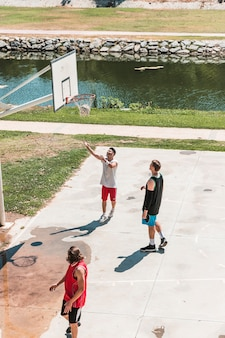 Three players looking at basketball falling from net