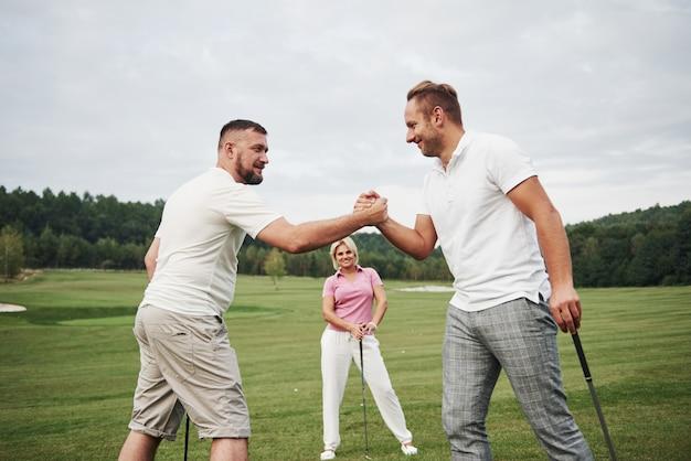골프 코스에서 3 명의 선수가 경기합니다. 팀은 축하하고 서로 악수합니다.