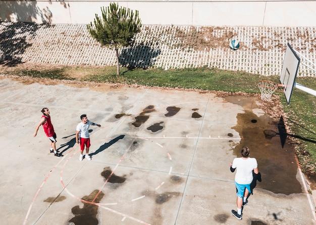 屋外のコートでバスケットボールをする3人の選手