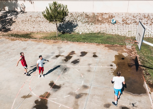 Three players playing basketball at outdoors court