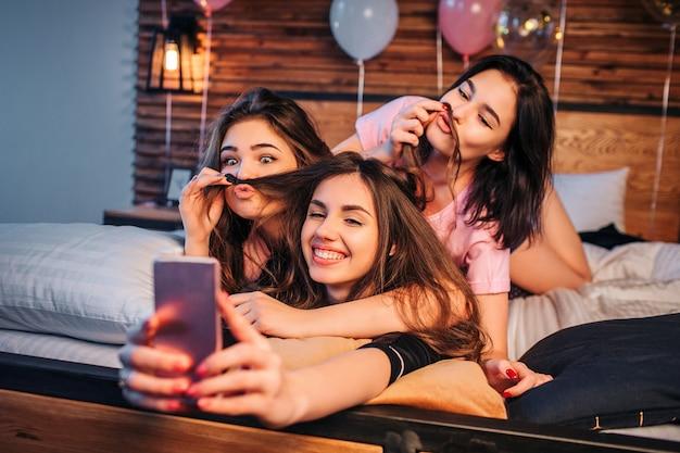 3 шаловливых молодой женщины принимая selfie на кровать в комнате. две модели играют с волосами третьей девушки. они выглядят, позируют и улыбаются. девушки выглядят счастливыми.