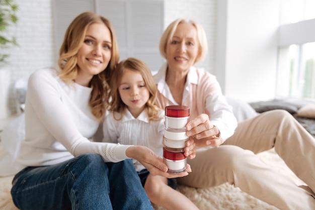막내부터 맏형까지 다양한 연령대의 유쾌하고 쾌활한 세 여성이 카펫에 앉아 크림 항아리로 탑을 만듭니다.