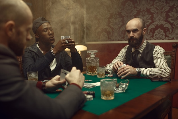 Three poker players with cards playing in casino. addiction, gambling house