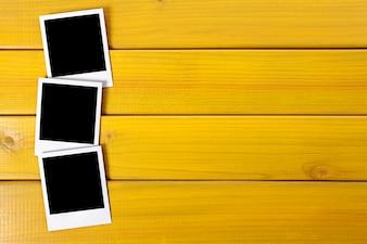 Three polaroid photo prints on a wood desk or table