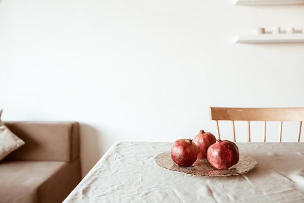 베이지 색 테이블 피복에 황금 접시에 세 석류