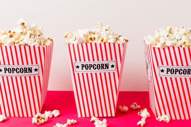 Three popcorn box filled with popcorns on pink background
