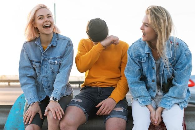 3人の前向きな友達が通りで笑っています
