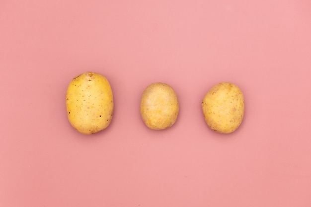 Three potatoes on pink background