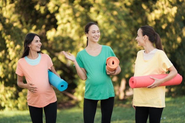 Three pregnant girls posing in a park with yoga mats in hand.
