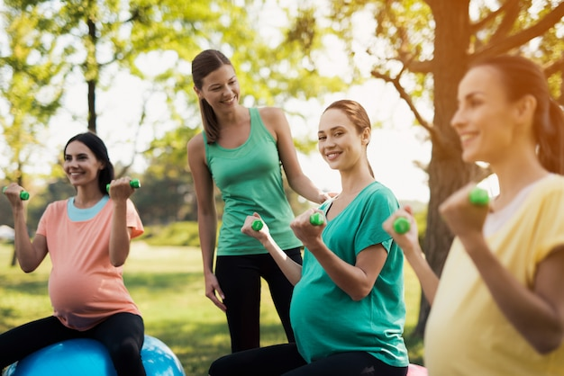 Three pregnant women are engaged in fitness in the park.