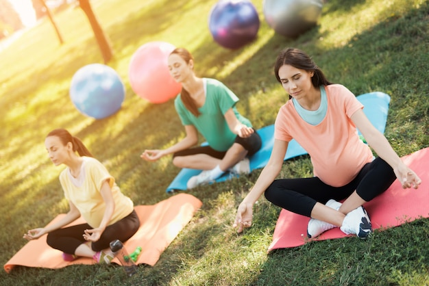 Three pregnant women sit on yoga mats in a lotus pose.