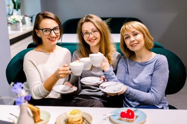 3人のかわいい白人のガールフレンドは、カフェでコーヒーを飲みながら一緒に時間を過ごし、楽しんで、ケーキやデザートを食べます。