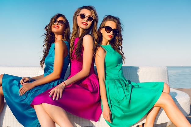 Three pretty friends in same colorful dresses posing near the beach