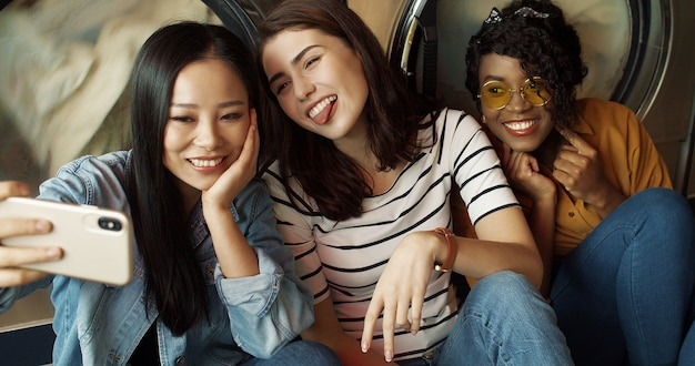 Three pretty mixed-races friendly girls at washing machines in washhouse smiling to smartphone camera, taking selfie photo. multiethnic beautiful woman making pictures with phone in laundry service.