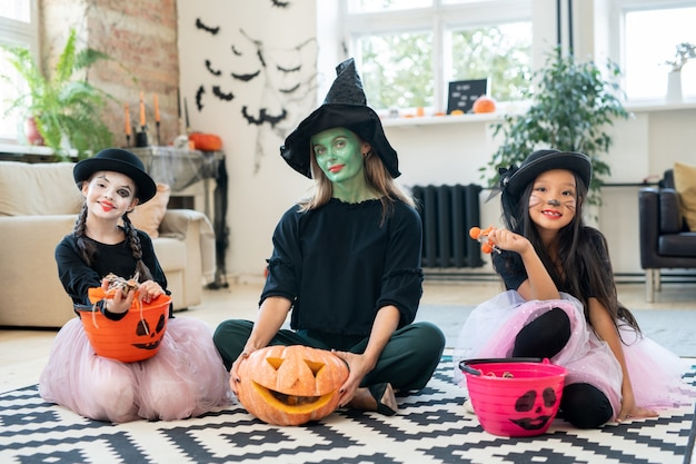 Three pretty witches sitting with trick-or-treating buckets on floor and looking at camera while enjoying halloween party