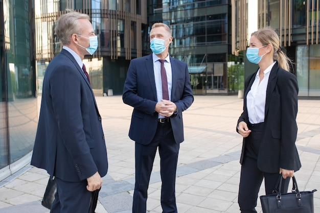 Трое профессиональных коллег по бизнесу в масках обсуждают сделку на улице. доверьтесь успешным менеджерам, которые стоят на улице и говорят о работе. концепция переговоров, защиты и партнерства