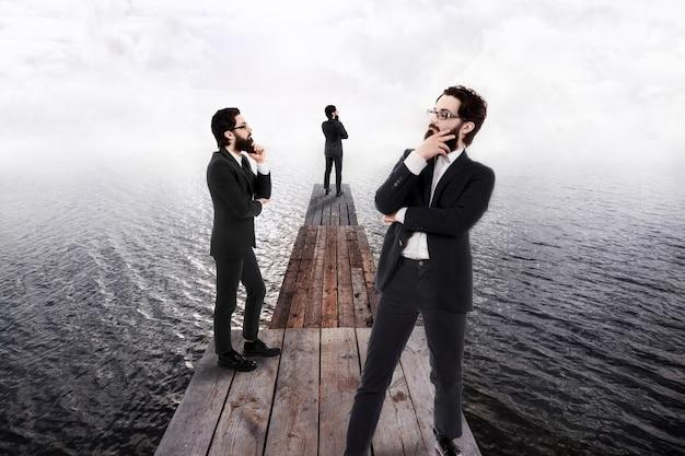 水に入る木製の桟橋に立っているスーツと眼鏡をかけた1人の物思いにふけるビジネスマンの3つの投影。思考と検索のアイデアの概念。