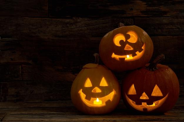 幸せそうな顔をした3つのカボチャのジャックランタンは、ハの中に燃えるろうそくを持ったハロウィーンのカボチャを刻みました...