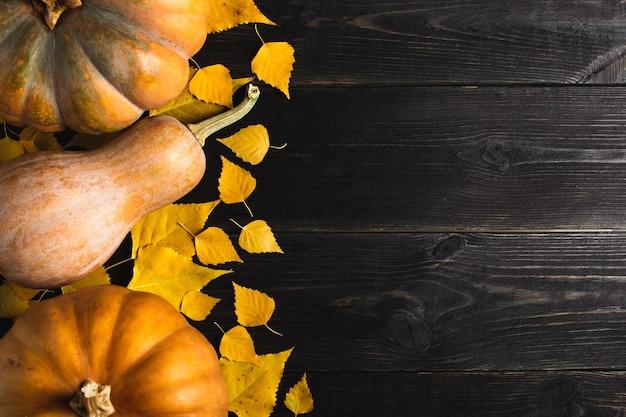 Три тыквы разных размеров на черном деревянном фоне с желтыми листьями. расположен с одной стороны. скопируйте пространство. вид сверху.