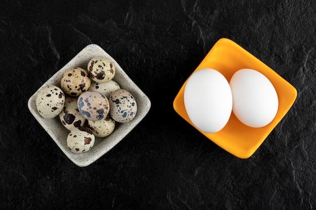 Три перепелиных яйца и куриные яйца на черной поверхности