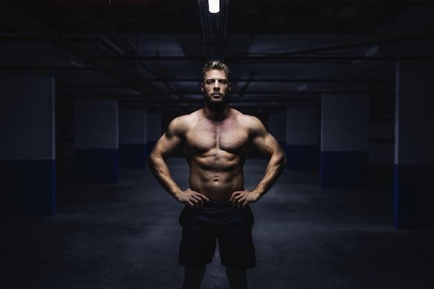 Три четверти длины топлес мускулистых шорт спортсмена, стоящего в гараже с руками на бедрах ночью. концепция городской жизни.