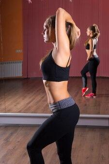 ミラー付きダンススタジオで頭の後ろに腕を伸ばして運動服を着ている若いブロンドの女性の4分の3の長さの側面縦断ビュー