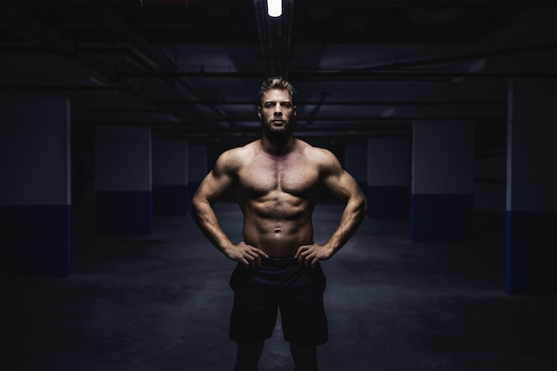 Three quarter length of topless muscular sportsman shorts standing in garage with hands on hips at night. urban life concept.