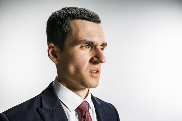 嫌悪感の顔を持ったビジネスマンの4分の3の肖像画。