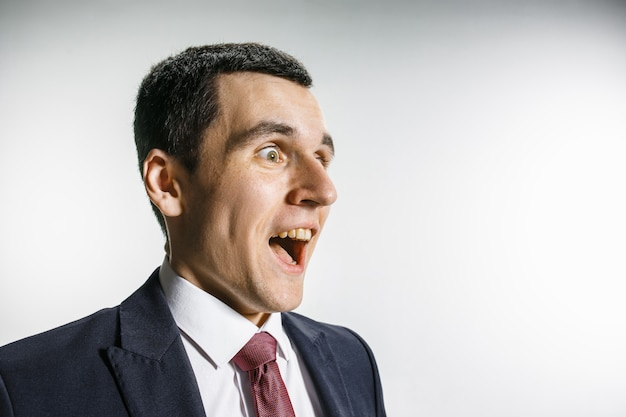 驚いて、笑顔のビジネスマンの4分の3の肖像画。カメラの前景をピアスで見る自信のあるプロフェッショナル。