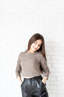 Three quarters length portrait of beautiful smiling brunette woman with long hair wearing brown shirt and black leather shorts, on white brick wall background, hands in pockets