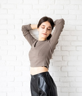 Three quarters length portrait of beautiful smiling brunette woman with long hair wearing brown shirt and black leather shorts, on white brick wall background