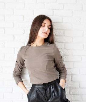 흰색 벽돌 벽 배경에 갈색 셔츠와 검은 가죽 반바지를 입고 긴 머리를 가진 아름 다운 미소 갈색 머리 여자의 3/4 길이 초상화, 주머니에 손