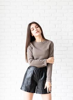 Портрет красивой улыбающейся брюнетки с длинными волосами в коричневой рубашке и черных кожаных шортах длиной в три четверти на фоне белой кирпичной стены