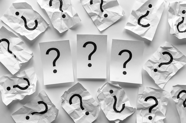 Three question marks surrounded by crumpled