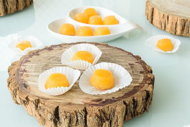 Три квиндины на деревянной доске. традиционная бразильская конфета с яичным желтком.