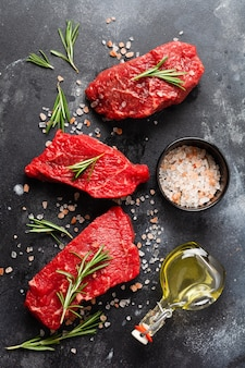 Three raw beef steak with spices, onions and rosemary on dark slate or concrete background. top view
