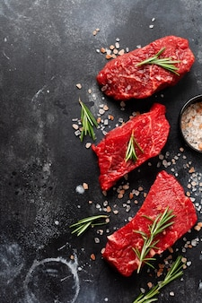 Three raw beef steak with spices, onions and rosemary on dark slate or concrete wall. top view