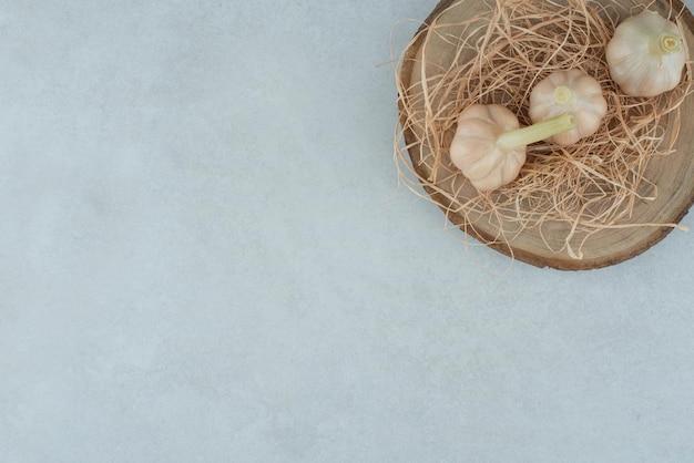 Three raw garlic on wood piece.