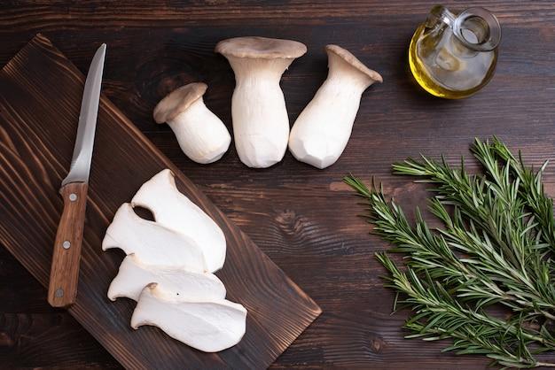 3개의 생굴 버섯, 로즈마리 잔가지, 도마에 버섯 조각