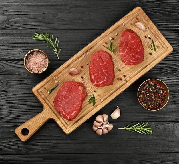 오크 나무 커팅 보드에 3개의 생 안심 또는 필레 미뇽 쇠고기 스테이크