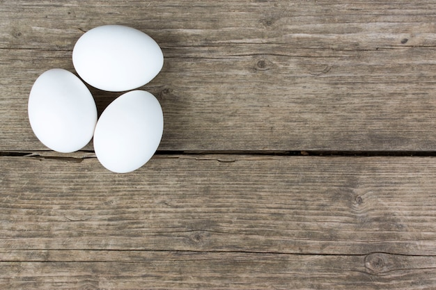 Three raw white hen eggs on old vintage wooden table