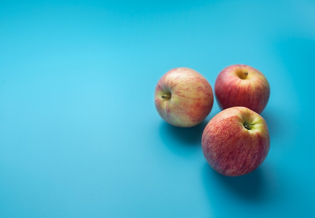 Three red apples on a blue