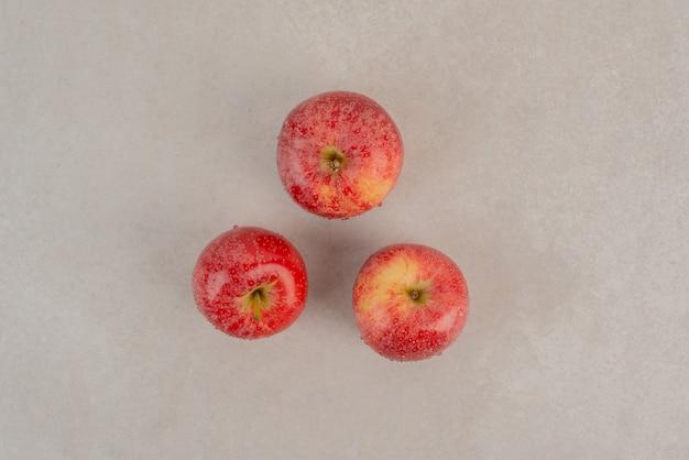 大理石の表面に3つの赤いリンゴ。
