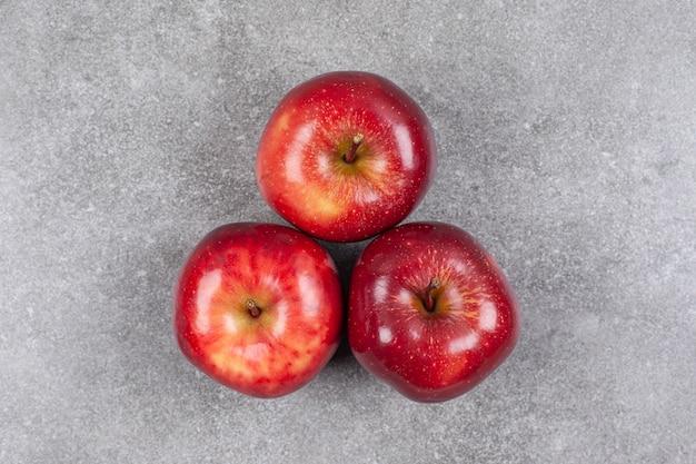 대리석 표면에 3 개의 빨간 사과