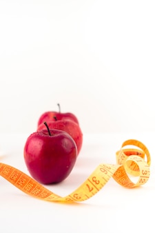 Three red apples with measuring tape on table