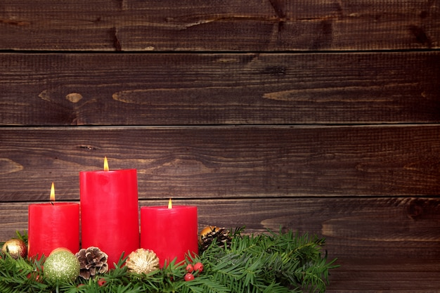 Three red candles with christmas decorations